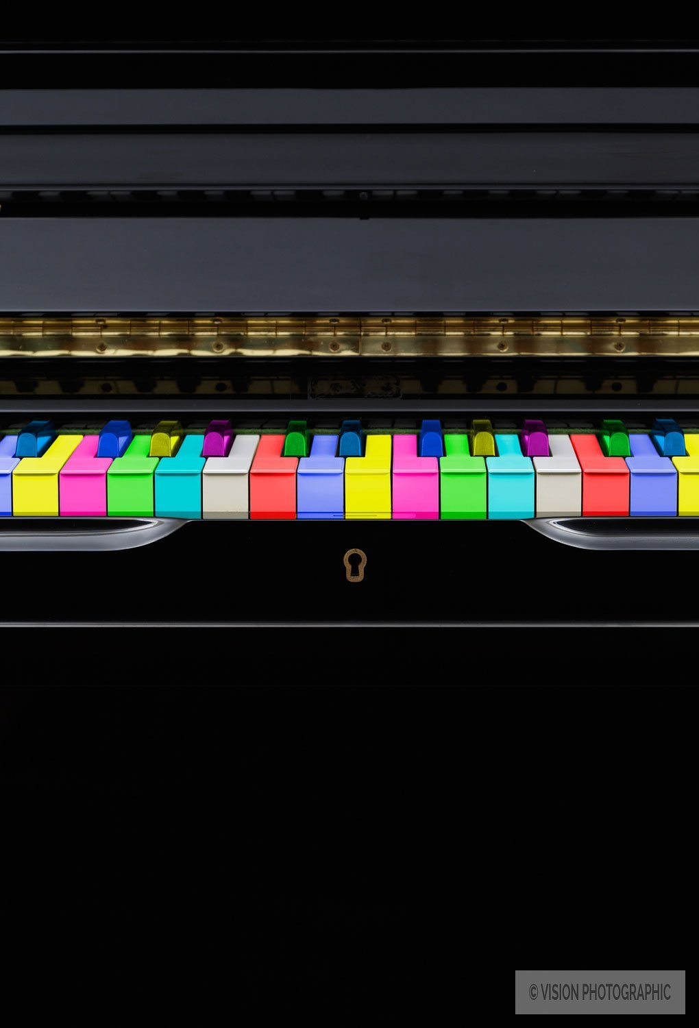 still life image of a piano with multicoloured keys